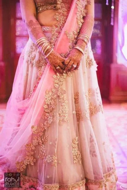 Day Wedding Lehenga Style | Creme Net lehenga with gold embroidery and studding and a pink net dupatta with gold border detail in embroidery for the Indian Bride's Day wedding | Curated by Witty Vows | source Rahul De Cunha Pictures