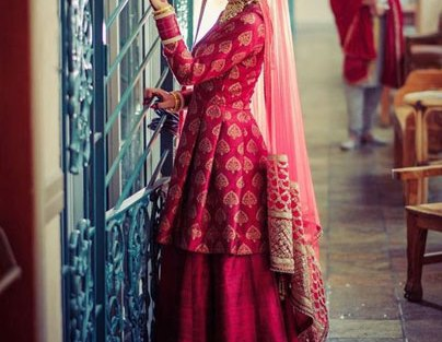 Gold and maroon silk brocade long peplum blouse with a plain silk lehenga and net dupatta with gold border | Curated by Witty Vows
