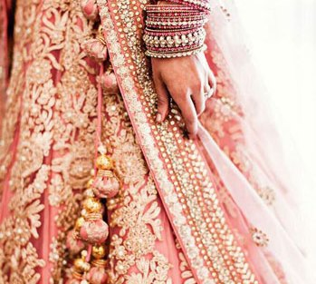 Beautiful blush coloured lehenga with gold embellishment all over in floral motifs and matching fabric and gold tassels | Curated by Witty Vows
