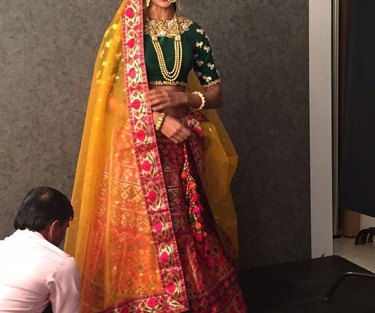 Green blouse with gold work on sleeves   Creme lehenga with bright multicolour embroidery and yellow net dupatta with matching embroidered border   Benzer Fashion   Curated by Witty Vows