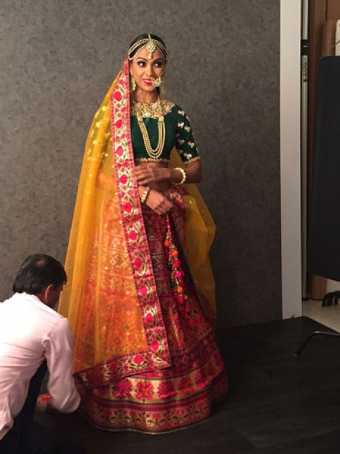 Green blouse with gold work on sleeves | Creme lehenga with bright multicolour embroidery and yellow net dupatta with matching embroidered border | Benzer Fashion | Curated by Witty Vows