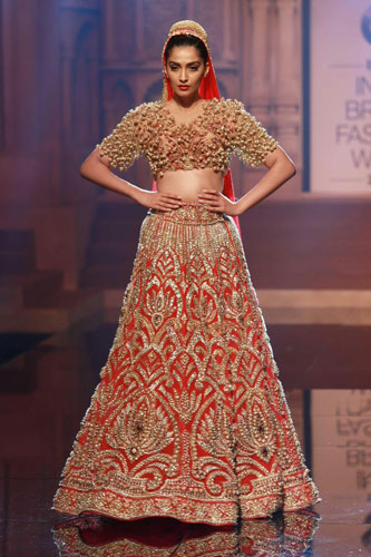 Red and gold stunning bridal lehenga with heavy embellishment in gold by Abu Jani and Sandeep Khosla | curated buy witty vows