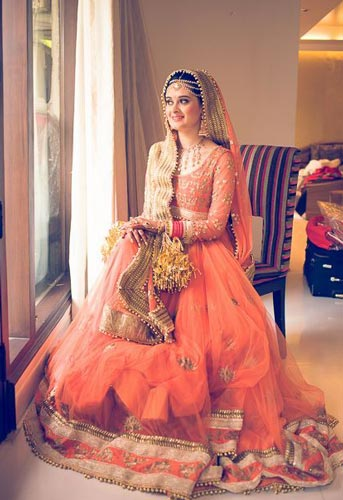 Day Wedding Lehenga Style | Pastel Light Peach orange net lehenga with gold handwork booties and dull gold and orange wide borders and gold trinkets | Curated by Witty Vows