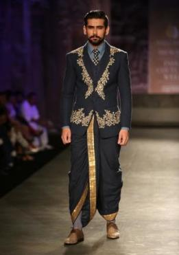 Fashion for the Indian Groom - Pair an embroidered jacket with a traditional Dhoti | Black and gold | Image source - Hindu | Ideas for Wedding Sherwani Designs for Men |Curated by Witty Vows