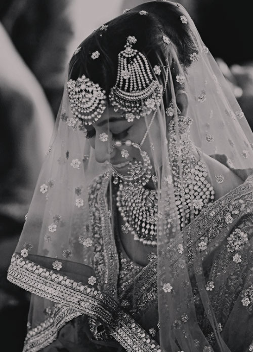 Stunning black and white shot of the bride in a veil Indian wedding | Curated by With Vows