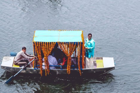The unconventional destination wedding baraat reception in a boat from the lakeside to the mandap decorated with marigold flowers for this colourful Indian Wedding | Jonathan & Subhashree | Cureated by Witty Vows