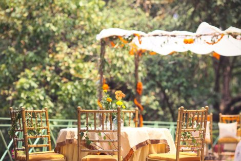 Yellow round tables with marigold centrepieces | Lakeside wedding - outdoor Indian wedding decor ideas | Signages with couple caricatures - ideas for Indian wedding details | A woodland theme forest destination wedding in the Hills | Bengali wedding by the lakeside | Traditional Bengali wedding ceremony at a destination | The beautiful green and marigold mandap by the lakeside | Genda flower decor ideas | Subhashree and Jonathan | Ideas | curated by Witty Vows