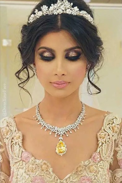 Indian wedding hairstyles for Indian Brides | A soft updo with loose curls framing the face and a tiara style dupatta drape