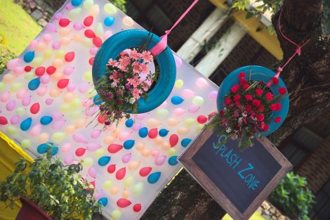 Cute corners for kinds in an Indian outdoor Mehendi setting with tyres with flowers | Jonathan & Subhashree | Curated by Witty Vows