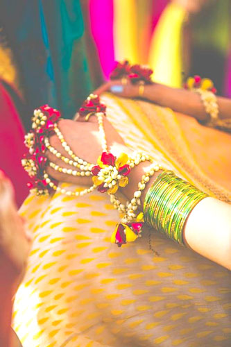 Yellow, Pink and white floral jewellery for mehndi | Hathphool bracelet for the bride | Mehendi and Wedding Accessories | Picture - Mahima Bhatia Photography | Curated by Witty Vows