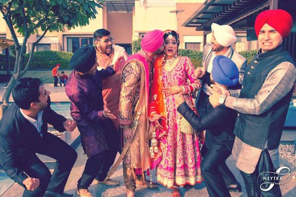Indian bride photo with her brothers stopping the groom from kissing her