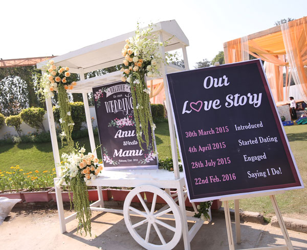 Anu weds Manu - a pretty day wedding in delhi| Pretty Indian Bride in an ombre ivory and blush peach lehenga with mint green accents and a mint green dupatta | pastel perfection | White cart with flower decoration and chalk board sign of how we met - our love story