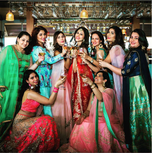 Mehndi photo shoot | New mehndi ideas from Kishwer Merchant's pretty daytime mehndi |Kishwer's Bridesmaids's shoot idea for Indian brides| bride in red lehenga with gold work on a bar with wine | Mehndi decor ideas and mehndi photoshoot ideas
