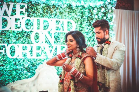 Indian Wedding Ideas from Suyyash and Kishwer's Wedding Reception | Kishwer in red lehenga with a gold blouse and detailing in mirror & Suyyash in a white tux | we decide on forever backdrop with letters white on green grass backdrop | Candid couple photo shoot ideas