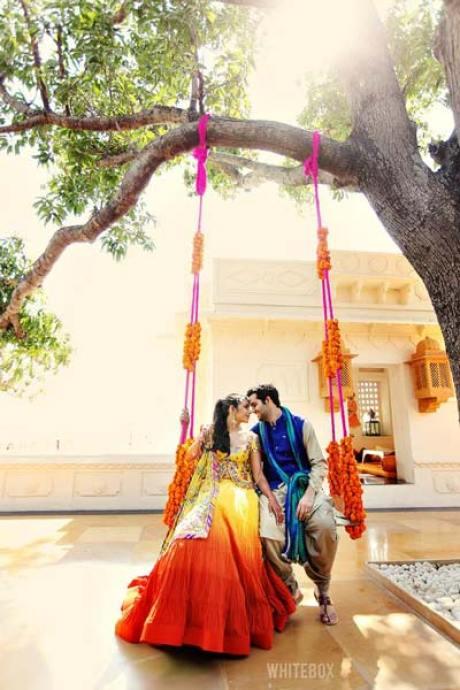 Mehndi jhoola and innovative mehndi decor ideas | beautiful mehndi swing bridal seat idea with bride in ombre lehengas | Photo by whitebox Studio