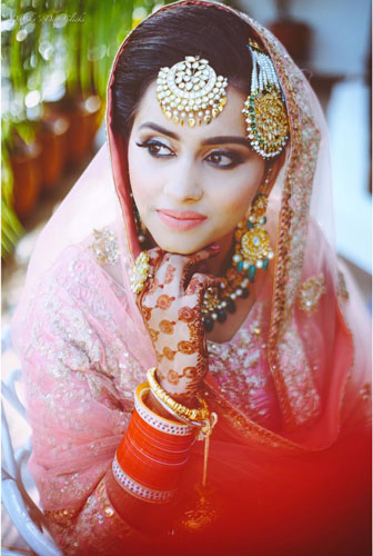Top Indian Bridal Makeup trends   Makeup for bride   Getting ready photo   wedding look - Pink and gold wedding lehengas   Kundan bridal jewellery   pretty Indian bride with day time makeup - pink lipstick and white Kajal highlights   Makeup idea + Jaali mehndi   Photo by - Deepika's Deep Clicks