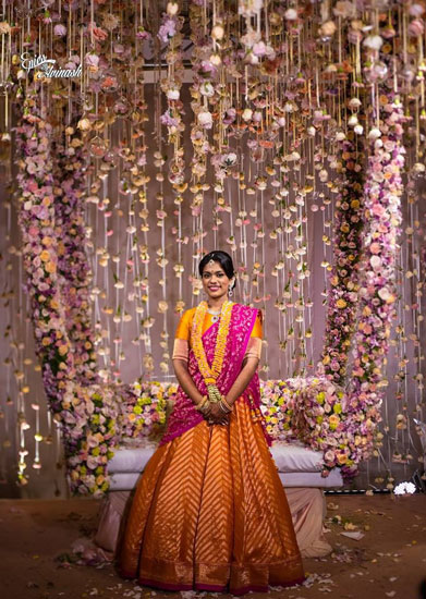 innovative mehndi decor ideas | Bridal seat chaise with a floral curtain in white Rajni flowers | South Indian wedding | Bride in Yellow and pink lehengas | Pastel floral string curtain in pale pink colours with a swing illusion | Photo by - Epics by Avinash