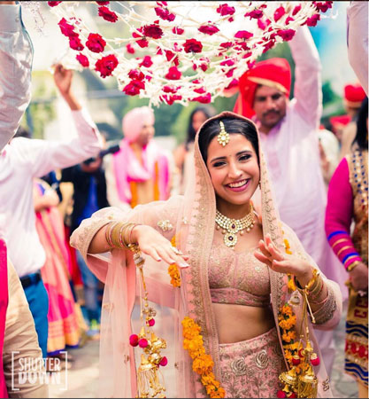 Happy Bride in blush coloured lehenga under a floral chadar | photo - shutter down photography