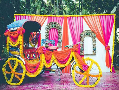 Indian Kitsch Mehndi Decor Ideas | Fun DIY Mehndi theme with super colourful Mehendi decor | Witty Vows | colourful rickshaw with marigold flowers