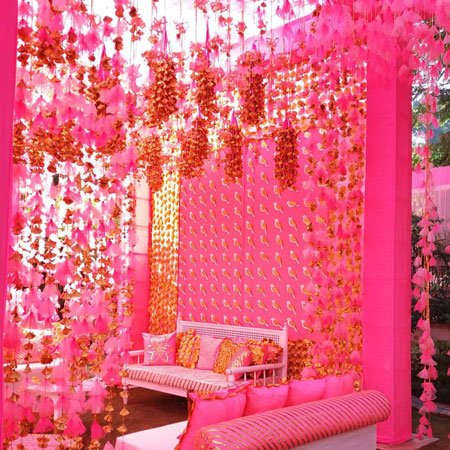 innovative mehndi decor ideas | beautiful mehndi Bridal seat sofa for bride with ghunghroo decor in pink and gold | Decor by Rani Pink