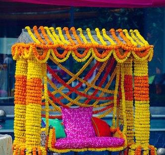 Mehndi jhoola and innovative mehndi decor ideas   beautiful mehndi swing bridal seat idea with bride on marble swing set dressed in marigold Photo by - Dot Dusk