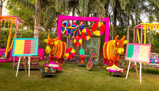 photo op with a Kitsch indian design | colourful marigold bulls, colourful pinwheels in fabric and a bicycle with a colourful pot! | Indian wedding photoshoot ideas | Indian bride in pretty pink gown | Indian wedding photo booth ideas | Photo Op ideas | fun wedding photos |