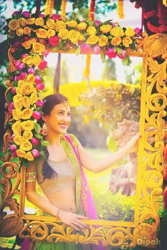 photo op with a colourful yellow photo frame with flowers and.a pretty Indian bride looking through | Indian wedding photoshoot ideas | Indian bride in pretty pink gown | Indian wedding photo booth ideas | Photo Op ideas | fun wedding photos | Dipak Studios