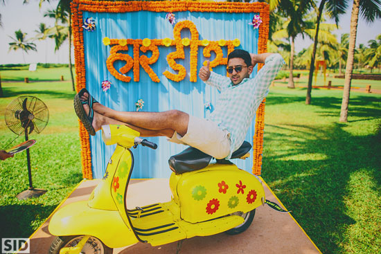 photo op with a colourful yellow scooter with marigold flower alphabets in Hindi | Indian wedding photoshoot ideas | Indian bride in pretty pink gown | Indian wedding photo booth ideas | Photo Op ideas | fun wedding photos | Total Siddharth photography