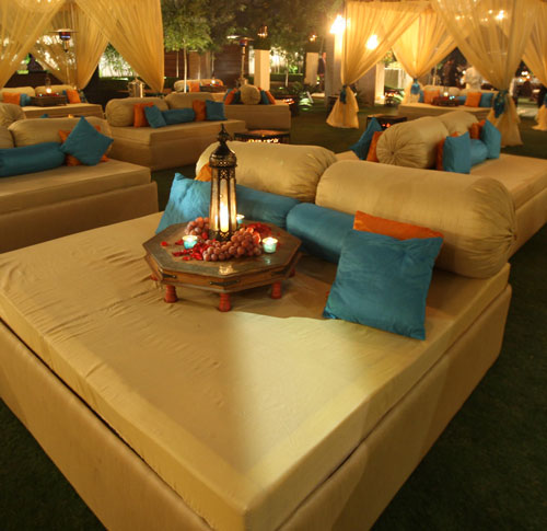 Sufi Night | Sangeet decor ideas | Free Sangeet Theme | decor ideas for sufi sangeet | Designed by E Factor Entertainment | creme seating for sangeet | ivory bed with blue and orange cushions and a lantern in the middle with fruits and rose petals