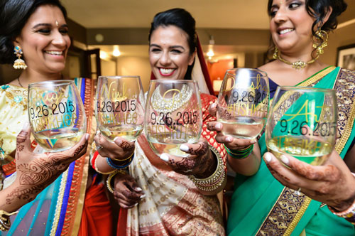 Indian bridesmaids duties | Bride's friends | BFF photos from Indian wedding | Indian bride with her bridesmaids toasting before the wedding in customised glasses wine | grey card photography