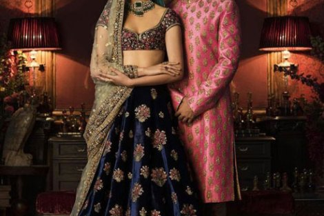 Coordinated outfits, Tips for Couple outfits | Bride in a velvet Sabyasachi blue lehengha and gold dupatta and groom in a salmon red sherwani