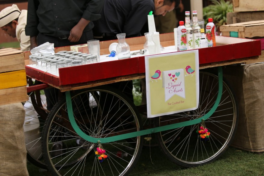 Colourful cart used as bar for Mehndi decor with a signage for Liquid assets