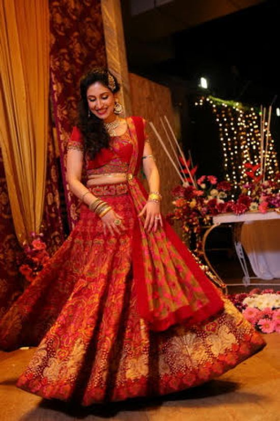 Indian bride doing a twirl in an all over embroidered red lehenga with a Kundan jhoomar