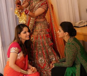 Indian bride dropping the kalira on her friends | bride in carrot red and gold Cabala work all over her lehenga paired with orange dupatta