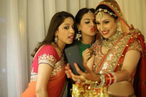 photos from etc bridal suite | brides getting ready shoot | Indian bride posing with her friends for a selfie before her wedding