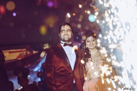 plush affairs photography | Peach gown for the Indian bride with flowers and shimmer | maroon and black tux suit for the Indian groom with a black bow tie | sparklers and fireworks at the couple entry