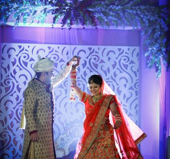 plush affairs photography | Jabalpur wedding | high school sweethearts | Divya and Nikhil | groom in a beige and cream sherwani with gold motifs and bride in a red and gold lehengas | Indian bride and groom twirling the bride | first dance