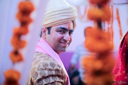 Indian groom looking through the marigold strings