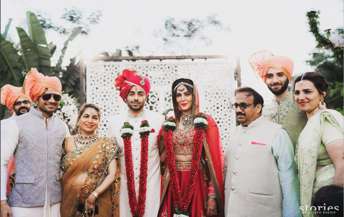 Mandana Karimi wedding | Mandana bride in a red and gold lehenga with rose jaimala | stories by Joesph Radhik | white jail backdrop