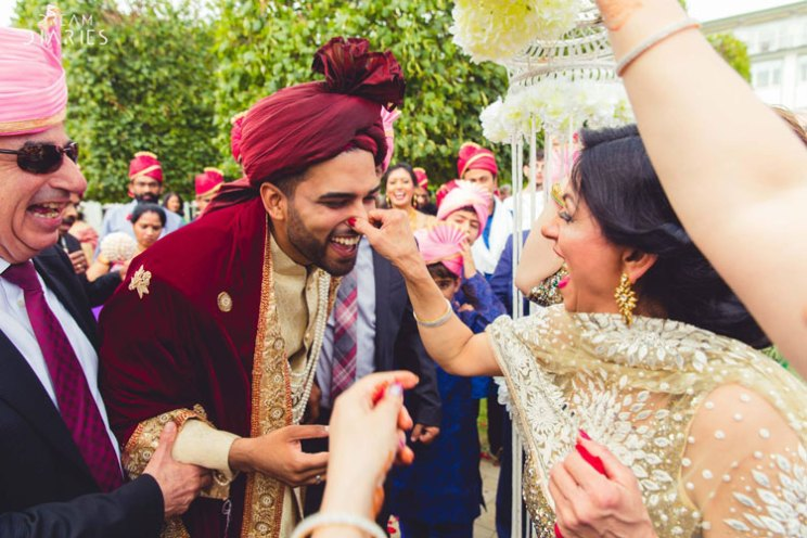 Indian bride's mother pinching the groom's nose | Mother of the bride photos