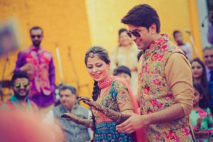 Purva and Sahil | wedding in delhi | Father daughter wedding photos | Indian couple wearing coordinated colour outfits | Bride and groom in Burgundy sherwani and lehenga with green and gold accents | Indian bride and groom in beige outfits with pink and blue and gold floral work on the waistcoat and blouse