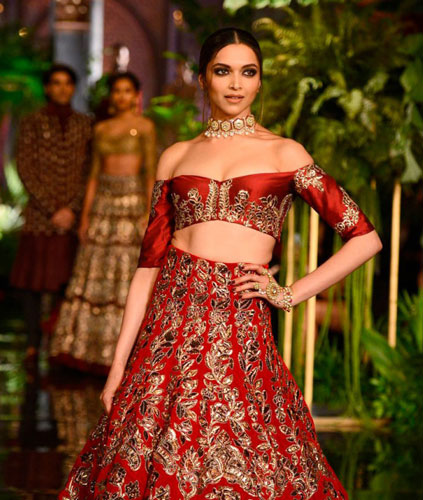 Latest blouse styles | new blouse styles to love | latest blouse designs for Indian brides | Indian bride with beautiful twisted braid with baby's breath flowers | Deepika Padukone in an off shoulder red and gold manish Malhotra outfit | off shoulder blouse for brides