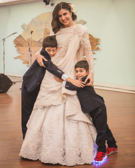 sherry Shroff wedding | Beach wedding vibe | sherry and her husband cutting a cake at their wedding | sherry Shroff in a customised gaurav gupta white lace lehenga for her wedding | bride hugs her nephews before the wedding