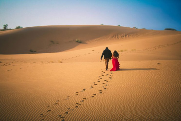 pre wedding shoot in Rajasthan   Bollywood style couple shoot   Veena and Vishal   Shoot (c) Candid Shutters  dreamy Indian wedding shoot in Jaisalmer   couple walking with footsteps on the sand in the desert