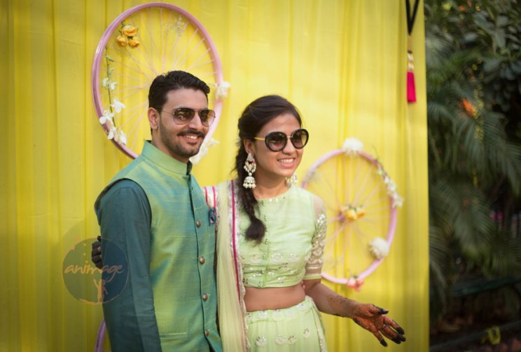 ⬆︎Anukriti and Siddharth | Delhi Wedding full of simple nd fun wedding ideas | Photo by AnImage Productions | Indian couple on a bike | Bride enters behind the groom on a bike with her mehndi on and floral jewellery | groom in green waistcoat and blue shirt | cycle tyres painted pink with flowers used for decor for the mehndi