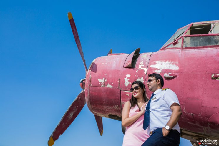 first anniversary idea, anupriya and ankit, aniversary photoshoot | Indian couple pose in front of a propellor plane in red