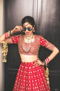 JyotPriya and Nishant | Punjabi wedding in Delhi | The boss bride in red lehenga with her shades on.