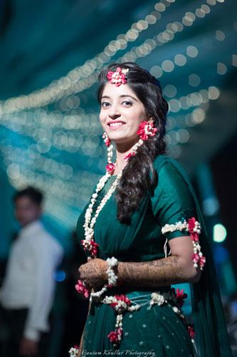Dhruv and Saina   Delhi wedding   bride wearing a green lehenga with floral jewellery and a flower maangtika