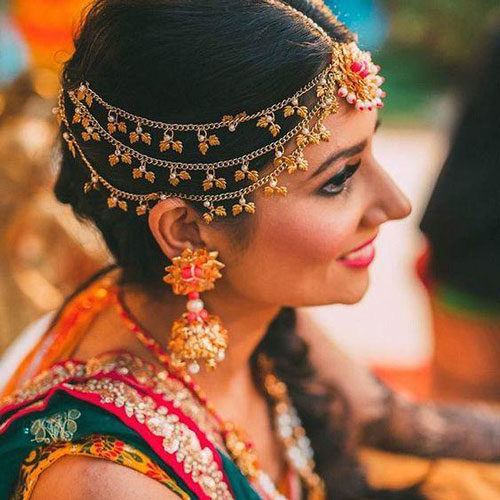 New mathapatti designs | Bridal jewellery trends | Pretty Gota mathapatti with a pink centre | shot by - Dot Dusk photography | Indian bride wearing pretty pink and gold gota earrings for her mehndi