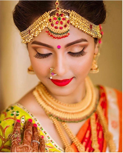 Pretty South Indian bride wearing gold traditional bridal jewellery with a ghunghroo mathapatti